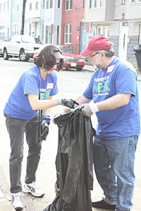 Marge Salazar, Associate Deputy Comptroller for Midsize Banks, and Hershel Lipow, Community Relations Expert, pick up debris on an Ivy City street.